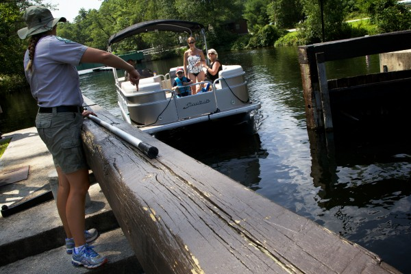 Assistant Park Ranger Lauren Hiller directs boats into the Songo Lock on Tuesday in Naples.