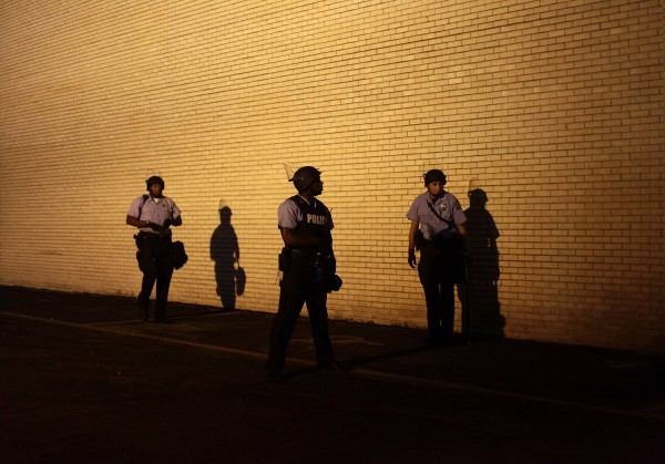 Police officers in riot gear watch demonstrators protesting against the shooting of Michael Brown from the side of a building in Ferguson, Missouri August 19, 2014.