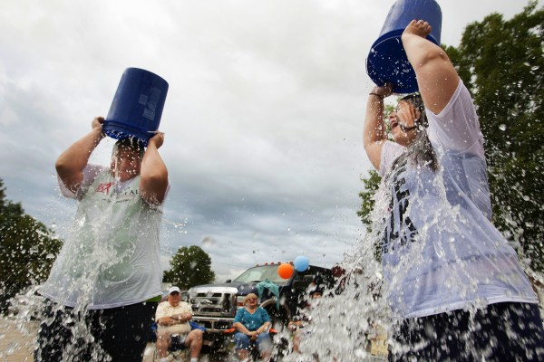 Heidi Klenowski (left) and Jessie Savage dump buckets of ice water on their heads as part of the ASL Ice Bucket Challenge on Friday at Carrier's restaurant in Bucksport.