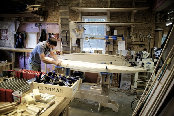 Luke Cushman planes the edge, or rail, of a wooden surfboard at his shop in Old Town. By day Cushman is a carpenter usually working long hours on MDI. By night he builds cedar surfboards in a shop next to his home on Pushaw Lake.