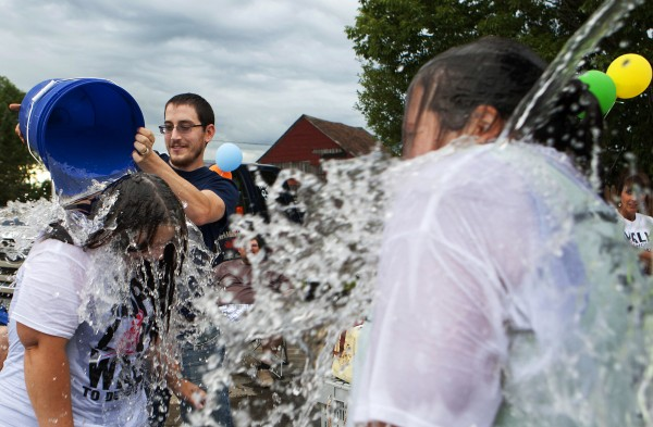 Dustin Carlisle (center) dumps a bucket of ice water on Jessie Savage (left) while Heidi Klenowski gets drenched by Paul Klenowski Jr. as part of the ASL Ice Bucket Challenge on Friday at Carrier's restaurant in Bucksport.