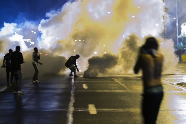 On Sunday, a protester reaches down to throw back a smoke canister as police clear a street after the passing of a midnight curfew meant to stem ongoing demonstrations in reaction to the shooting of Michael Brown in Ferguson, Missouri.