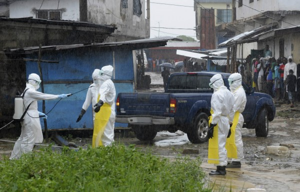 Health workers wearing protective clothing disinfect themselves after an abandoned dead body presenting with Ebola symptoms was found at Duwala market in Monrovia on August 17, 2014.