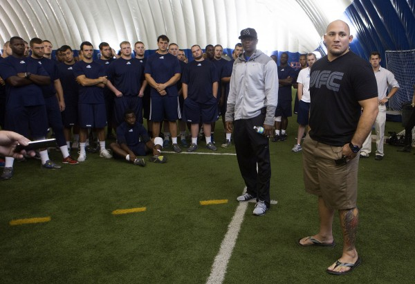 Ovince Saint Preux (center) and Shawn Jordan speak to University of Maine football players during a meet-and-greet at the campus in Orono Thursday.