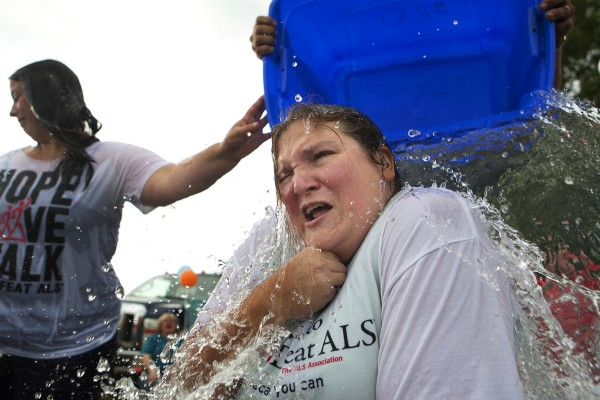 Heidi Klenowski (right) winces as ice water is dumped on her head by Dawain Moody as part of the ASL Ice Bucket Challenge on Friday at Carrier's restaurant in Bucksport.