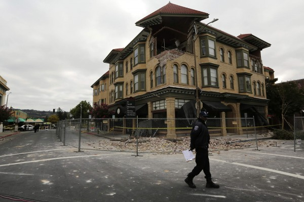 A security officer patrols an area in front of a building damaged by Sunday's magnitude 6.0 earthquake in Napa, California August 25, 2014.