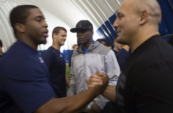 Shawn Jordan (right) and Ovince Saint Preux (center) are thanked by University of Maine football players following a meet-and-greet at the campus in Orono Thursday.