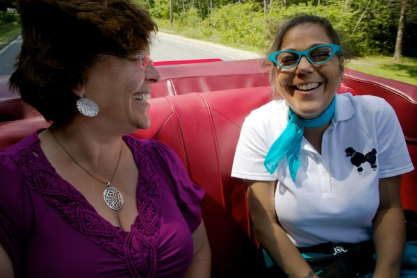 Nancie Boudreau-Smith (left) and daughter Ann Day laugh in the back seat of a 1967 Chevy Camaro in Freeport on Sunday. Boudreau-Smith is putting together a picture book of classic Maine cars to help raise money for her daughter's liver transplant.