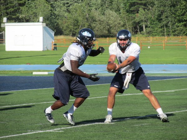 Quarterback Drew Belcher (right) of the University of Maine fakes a handoff to tailback Jerickson Fedrick during Tuesday's practice in Orono. Belcher is among four freshmen competing for playing time this season.