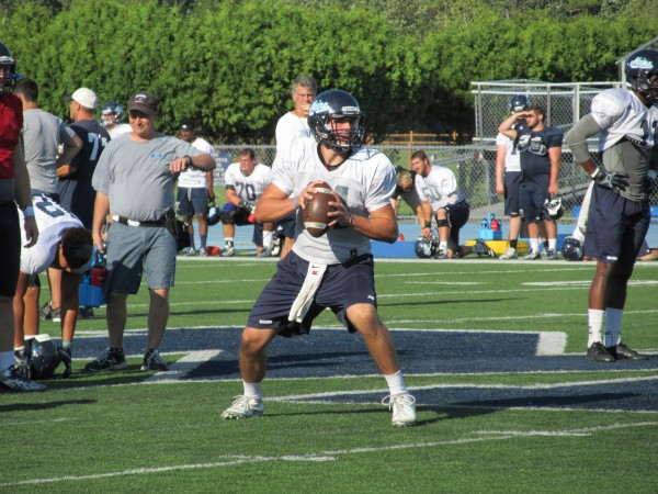Drew Belcher of the University of Maine sets up to throw a pass during Tuesday's football practice session on Morse Field in Orono. The quarterback is among four freshmen competing for playing time this season.