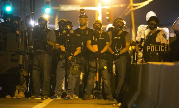 Police officers keep watch while demonstrators (not pictured) protest the death of black teenager Michael Brown in Ferguson, Missouri August 12, 2014.
