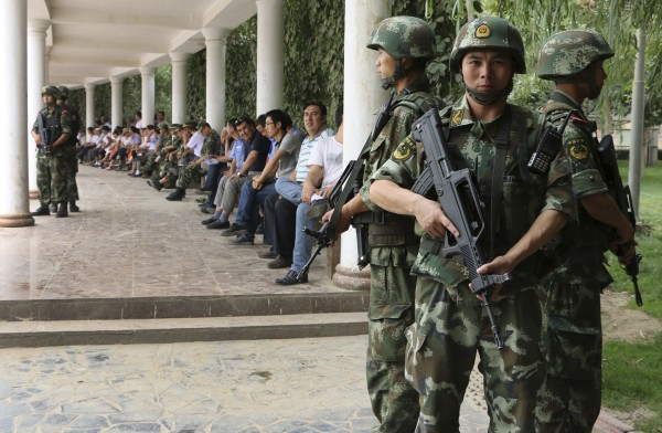 Paramilitary policemen stand guard during a ceremony to award those who the authorities say participated in &quotthe crackdown of violence and terrorists activities&quot in Hotan, Xinjiang Uighur Autonomous Region August 3, 2014.