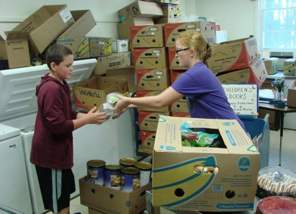 Boden Gould, left, and Hannah Gates stock a freezer at the Bath Food Pantry on Aug. 24. The pantry must find a new home because of the possible sale of the Neighborhood United Church of Christ.