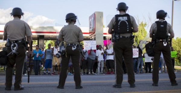 Police officers watch as demonstrators protest the death of black teenager Michael Brown in Ferguson, Missouri August 12, 2014.