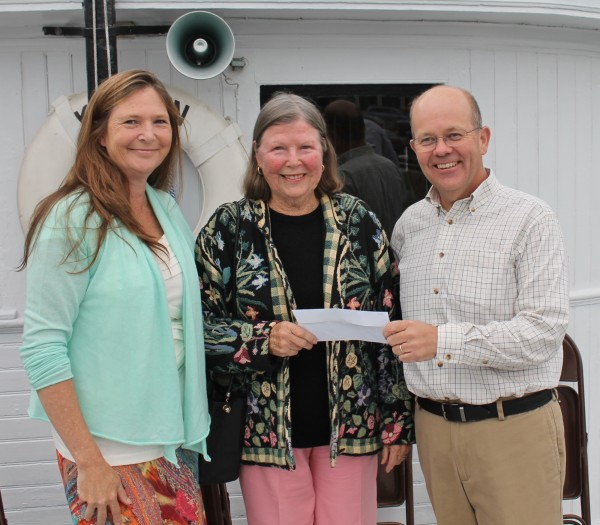 "The family of the late Louis O. Hilton presented a check for $250,000 to the Moosehead Marine Museum toward the maintenance of the Katahdin at the steamship's 100th birthday celebration on Friday in Greenville. Pictured, from left, Hilton's daughter Karen Fresne, his widow, ""B"" Hilton, and Luke Muzzy, chairman of the museum's board of directors."