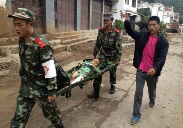 Paramilitary policemen carry an injured child on a stretcher as they carry out rescue operations after an earthquake hit Longtoushan township of Ludian county, Yunnan province on Saturday.
