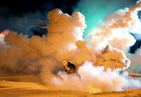 A protester takes shelter from the tear gas exploding around him in Ferguson, Mo., on Wednesday, Aug. 13, 2014.