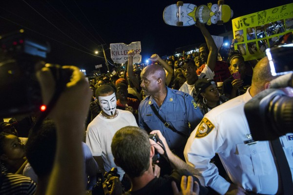 Missouri State Highway Patrol Captain Ron Johnson speaks to a protester wearing a &quotGuy Fawkes&quot mask while he walks through a peaceful demonstration as communities continue to react to the shooting of Michael Brown in Ferguson, Missouri August 14, 2014.