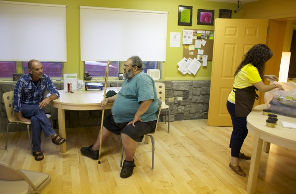 Mike Boutin (left) talks with patient Ed Barrood at the newly remodeled Wellness Connection of Maine medical marijuana dispensary in Brewer.