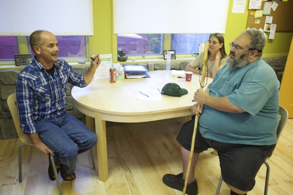Mike Boutin (left) talks with his wife Tawni and patient Ed Barrood at the newly remodeled Wellness Connection of Maine medical marijuana dispensary in Brewer.