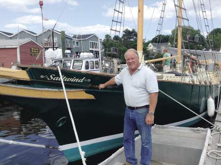 Dwight Raymond stands beside the boat he saved, the Salt Wind.