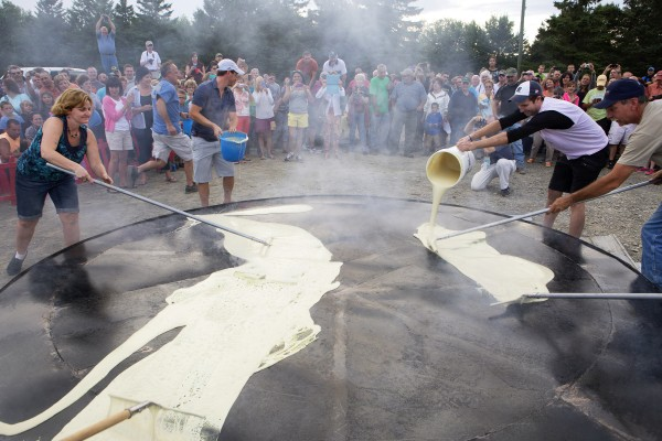 Bouchard crew members pour ploye mix onto a hot skillet to make the world's largest ploye at Riverside Park in Fort Kent on Aug. 8 as part of the celebration of the 2014 World Acadian Congress.
