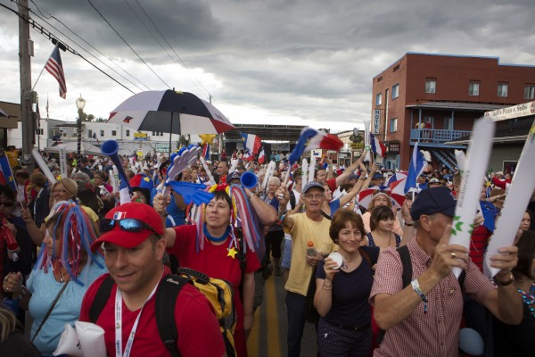 People show off Acadian pride while marching in the Tintamarre on Friday on Main Street in Madawaska.