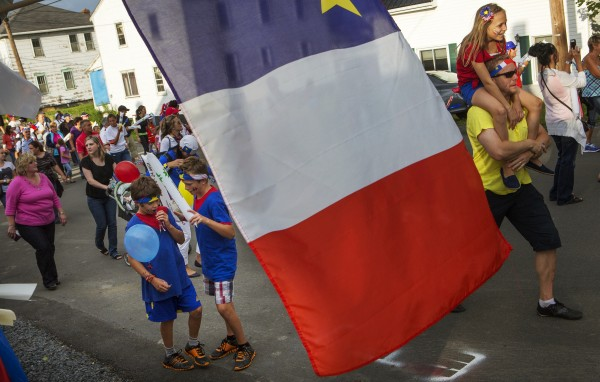 The Acadian flag hangs as people march in the Tintamarre on Friday on Main Street in Madawaska.