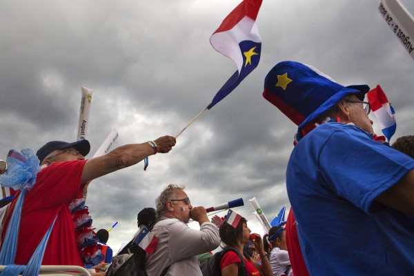 Celebrators wave Acadian flags and blow vuvuzelas during Tintamarre on Friday on Main Street in Madawaska.
