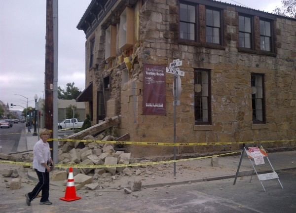 An unidentified woman walks past damage to a downtown building in Napa, California, on Sunday.