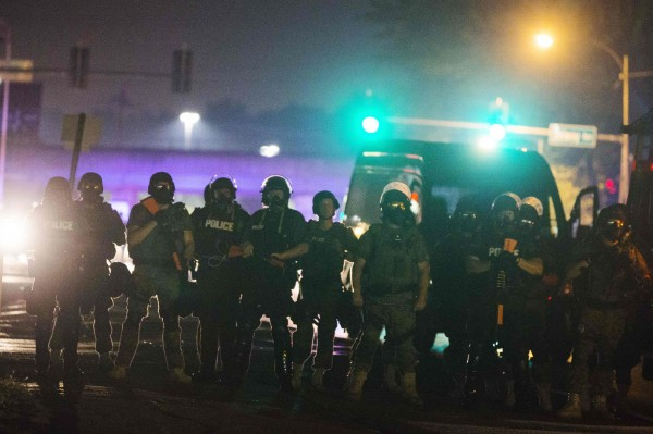 Police officers line up across the street early Saturday as they maintain their distance from protesters during demonstrations to protest against the shooting of Michael Brown in Ferguson, Missouri.