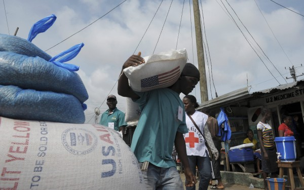 A resident of West Point neighborhood, which has been quarantined following an outbreak of Ebola, carries a sack of food rations from the United Nations World Food Programme in Monrovia August 28, 2014.