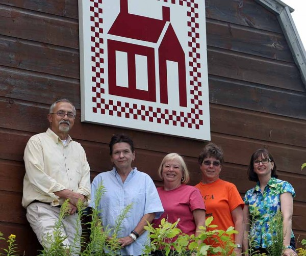 "The Houlton Higher Education Center recently erected a ""barn quilt block"" on a shed at the school to become part of the Friends and Needles Quilt Guild's Northern Maine Quilt Barn Trail. Showing off the new square are (from left) Chuck Ames, Toni Eppley, Jennifer Metzger, Jean Kervin and Bernadette Farrar."