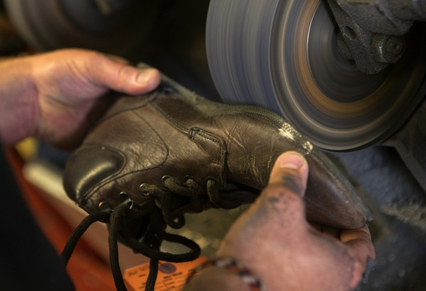 Yankee Cobbler's Jonathan Lambert grinds down a sole of a shoe to be replaced Thursday at his shop in Bangor. Lambert has been a cobbler for around 10 years.
