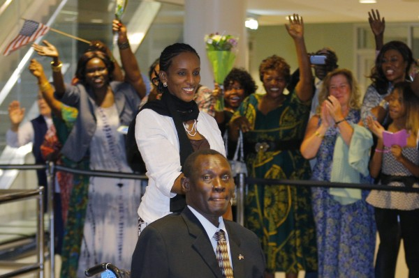 Mariam Yahya Ibrahim (center) and her husband Daniel Wani (bottom) are greeted by a cheering crowd of people as they arrive at the airport on July 31 in Manchester, New Hampshire.