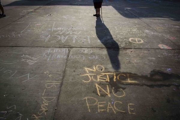 A man with a walking stick passes protest messages written in a parking lot before the announcement of the name of the officer involved in the shooting of Michael Brown on Friday in Ferguson, Missouri.