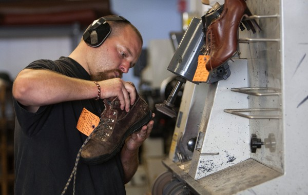 Yankee Cobbler's Jonathan Lambert works to grind down a sole of a shoe Thursday at his shop in Bangor. Lambert has been a cobbler for about 10 years.
