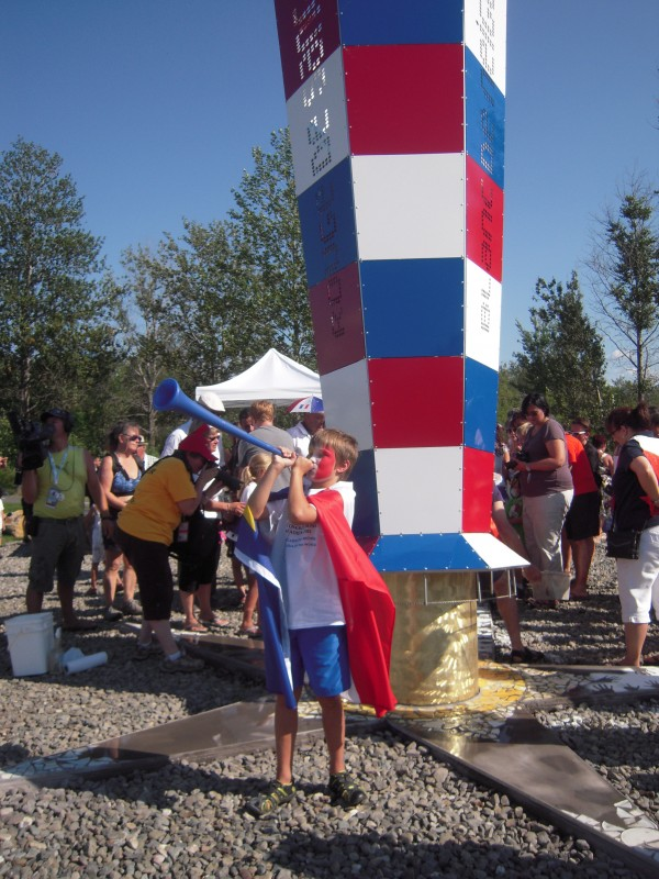 A sculpture by Pohenegamook artist Francois Maltais in the Parc Clair Soleil in Cabano, Quebec, forms a backdrop for Alexis Ruest of Edmundston, New Brunswick, the boy pictured on promotional materials of the 2014 World Acadian Congress, during Aug. 24 closing ceremonies.