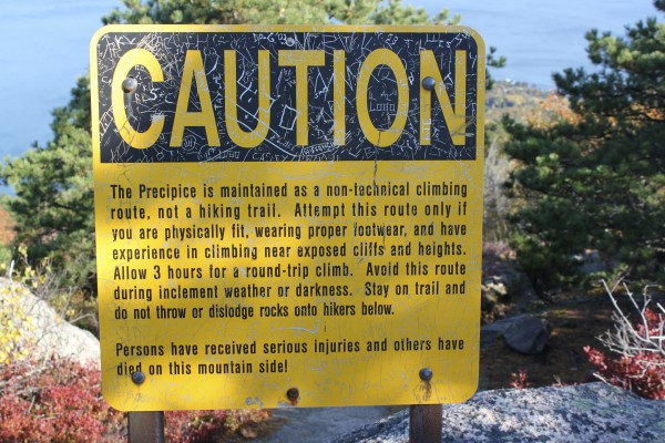 A caution sign stands at the top of Champlain Mountain in Acadia National Park as a warning to hikers descending the steep Precipice Trail down the east face of the mountain.