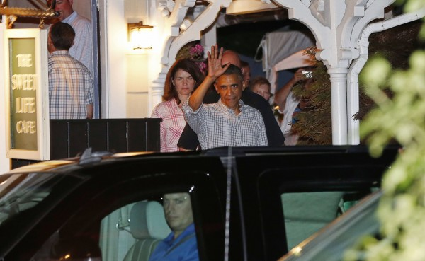 President Barack Obama waves as he departs a restaurant in Oak Bluffs at Martha's Vineyard, Massachusetts August 12, 2014.  The Obamas are on a two-week vacation to the Vineyard.