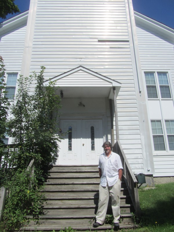Peter Davis stands on the steps of the 1851-built church in Rockland.