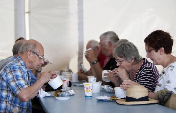 People enjoy chicken stew and ployes Friday during the 2014 Acadian World Congress in Edmundston, New Brunswick. Chicken stew and ployes are traditional Acadian dishes.