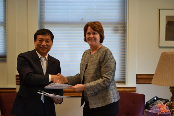 Yanbo Zhou, chairman of the Siyuan University board, and University of Maine at Presque Isle president Linda Schott shake hands after signing an agreement on Wednesday, Aug. 13, to establish a transnational college in China. The joint college, expected to be in place by fall 2015, will offer degrees in business, education and environmental studies. Graduates from this college will receive degrees from both UMPI and Siyuan. The new agreement expands upon the collaborative efforts between the two institutions, which have maintained a formal relationship since 2009.