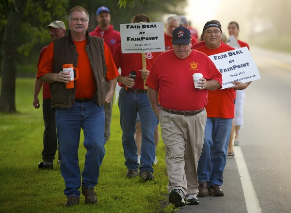 From left, Jim Feeney a FairPoint technician and Bob Toole march during a picket in front of FairPoint Communications in Bangor Tuesday morning. Employees conducted an informational picket a day before unions and the company meet for negotiations.