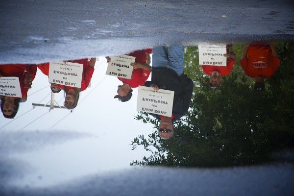 A reflection of FairPoint employees is seen in a puddle in front of FairPoint on Odlin Road in Bangor. The workers conducted an informational picket a day before unions and the company will meet for negotiations. The picketing is fueled by Fairpoint's proposal to hire out-of-state contractors.