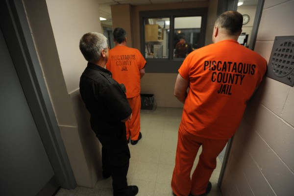Piscataquis County corrections officer Jeffery Starbird (left) waits in a hallway with two inmates before escorting them back to their cells during mail and medication call at the booking room of the jail in 2010.