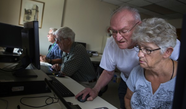 Class instructor Joe Mizda (left) helps Flow Hawkes with uploading her photos to her Facebook account during a class to help senior citizens use social media and computers Thursday at the Hammond Street Senior Center in Bangor.
