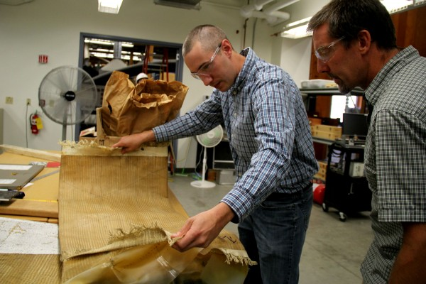 Josh Clapp, a doctoral candidate at UMaine, unfolds the material that may be used by NASA to build a device that slows down a space craft as it enters Mars' atmosphere. Clapp and Bill Davids (right) are conducting tests on the material to predict how it will react under pressure.