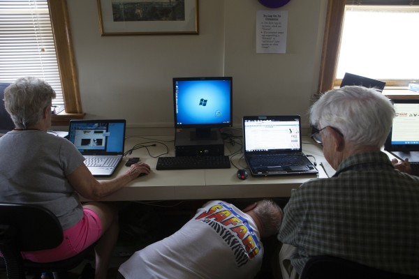 Class instructor Joe Mizda (center), helps Mel McClure (right) plug his computer into the printer while Flow Hawkes uploads photos during a class to help senior citizens use social media and computers Thursday at the Hammond Street Senior Center in Bangor.