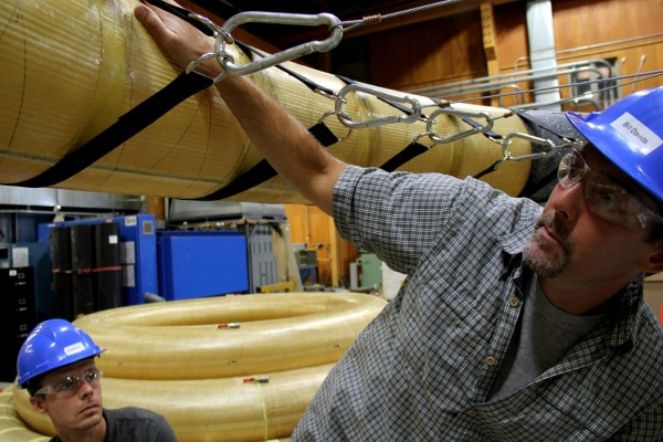 Bill Davids (right), a professor at UMaine and Andy Young, a doctoral candidate, examine a piece of device that may be used on space missions. The clamps attached to the black straps around the tube can be pulled inward, allowing the scientists to predict how the device will react under pressure.